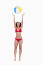 Attractive woman in bikini throwing a beach ball Royalty Free Stock Image
