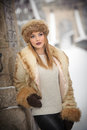 Attractive woman with brown fur cap and jacket enjoying the winter. Side view of fashionable blonde girl posing against bridge