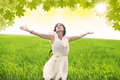 Attractive woman celebrate spring in green field looking up the skhy and Stock Image