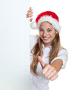 Attractive woman with christmas hat showing thumb behind a signboard laughing long blond hair and funny on white background Stock Images