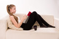 Attractive woman with a coffee cup lying on a sofa blonde Stock Photos