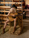 Attractive woman with country look, indoors shot, american country style. Blonde girl with black cowboy hat and guitar