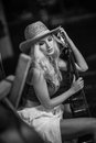 Attractive woman with country look, indoors shot, american country style. Girl with straw cowboy hat and guitar. Beautiful blonde Royalty Free Stock Photo