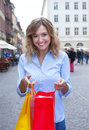 Attractive woman with curly blond hair and shopping bags in the city