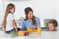 Attractive woman cutting an orange for her children women in the kitchen Stock Photos