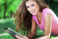Attractive woman with digital tablet lying on grass smiling Royalty Free Stock Images