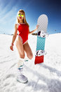 Attractive woman dressed in swimsuit with snowboard on the slope Royalty Free Stock Photo