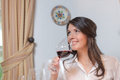 Attractive woman drinking red wine young brunette a glass of and looking away to the left of the camera Stock Photo