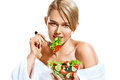 Attractive woman eating healthy vegetable salad from transparent crockery.