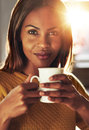 Attractive woman enjoying an energising coffee black cup of holding the mug in her hands as she looks at the camera with a quiet Stock Photos