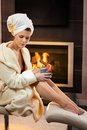 Attractive woman in front of fireplace Stock Photography