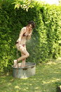 Attractive woman in garden takes a cold shower
