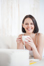 Attractive woman having coffee at home lounging with good book mature drinking tea and reading book on couch smiling and looking Stock Photography