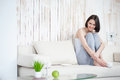 Attractive woman having coffee at home taking things easy today young relaxing on sofa with cup of Stock Photo