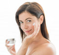 Attractive woman in her forties applying cream beautiful mature lady using lotion to prevent wrinkles Stock Images