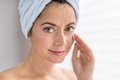 Attractive woman in her forties removing make up portrait of a beautiful mature lady using a cotton pad to clean skin and remove Stock Images