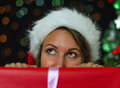 Attractive woman hiding behind a christmas gift Royalty Free Stock Images