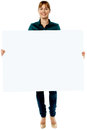 Attractive woman holding blank ad board full length shot of a presenting whiteboard Royalty Free Stock Photos