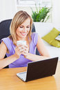 Attractive woman holding coffee and using laptop Royalty Free Stock Photo