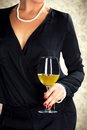 Attractive woman holding glass of white wine dressed in black and pearls Royalty Free Stock Images