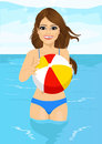 Attractive woman holding an inflatable striped ball standing in water
