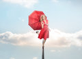Attractive woman holding umbrella in the sky Stock Photos