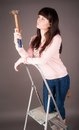 Attractive woman on ladder with hammer pretty girl a in her hand Royalty Free Stock Images