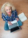 Attractive woman with laptop and book on the floor Stock Images