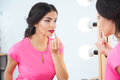 Attractive woman looking at mirror and applying red lipstick tolips Royalty Free Stock Photo