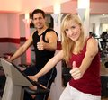 Attractive woman and a man cycling in a gym Stock Photos