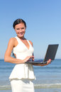 Attractive woman with notebook on the beach Stock Photos