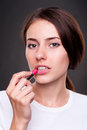 Attractive woman painting her lips Stock Photography