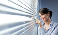 Attractive woman peeking through blinds Royalty Free Stock Image
