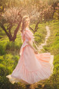 Attractive woman in pink dress enjoying the nature and walking bloom garden on sunset freedom concept Royalty Free Stock Photography