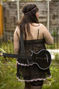 Attractive  woman playing guitar standing at Stock Photography