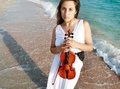 Attractive woman playing violin on beach Royalty Free Stock Photo