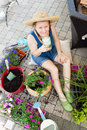 Attractive woman potting up houseplants in spring sitting on a brick patio surrounded by plants fertile soil and containers Stock Photo