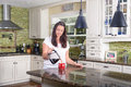 Attractive woman pouring homemade coffee for two in modern sunny kitchen Royalty Free Stock Photo