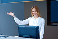 Attractive woman receptionist making friendly gesture at reception desk looking at camera and welcome Stock Image