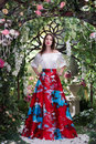 Attractive woman in red skirt in floral garden. Fairy tale Royalty Free Stock Photo