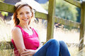 Attractive woman relaxing on walk in countryside smiling at camera Stock Photo