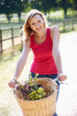 Attractive woman riding bike along country lane close up of smiling at camera Stock Image
