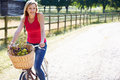 Attractive woman riding bike along country lane in daylight smiling Stock Images