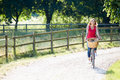 Attractive woman riding bike along country lane on her own smiling Royalty Free Stock Images