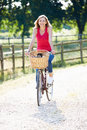 Attractive woman riding bike along country lane looking to camera smiling Royalty Free Stock Photo