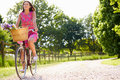 Attractive woman riding bike along country lane smiling Stock Image