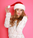 Attractive woman in santa hat in studio on pink background Stock Photo