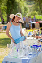 Attractive woman shopping for antiques provence france in a large floppy sunhat and collectibles at an outdoor market and holding Stock Photos
