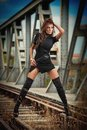 Attractive woman with short black dress and long leather boots standing on the rails with bridge in background. Fashion  sexy girl Royalty Free Stock Photo