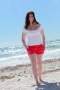 Attractive woman in shorts on the beach full length portrait of a barefoot standing front of blue ocean a hot summer day Royalty Free Stock Images